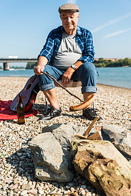 Germany, Ludwigshafen, portrait of smiling senior man barbecueing sausage on the beach - p300m1068833f by Uwe Umstätter