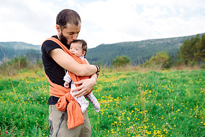 Father carrying baby girl outdoors in a baby sling - p300m1417139 by Gemma Ferrando