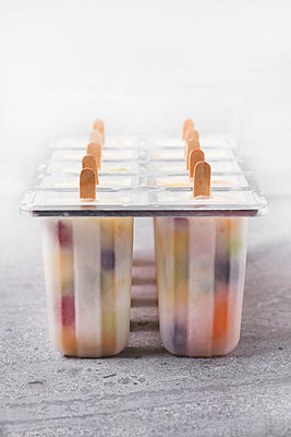Homemade fruits and yogurt ice lollies on marble - p300m1581177 von Retales Botijero