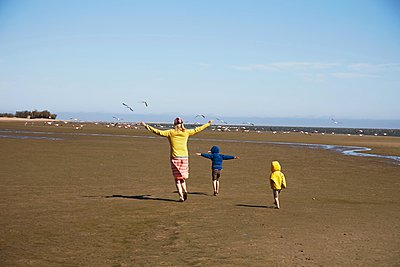 Mother and sons walking on beach, Walvis Bay, Namib-Naukluft National Park, Namibia - p429m1029882 by Stephen Lux