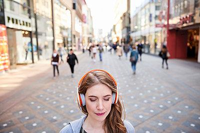 Frau in Fußgängerzone mit Kopfhörern - p890m1440024 von Mielek