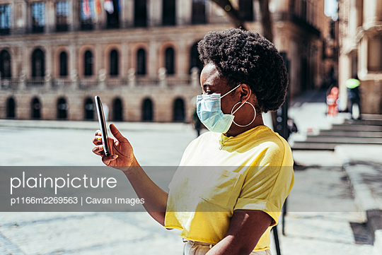 Portrait of black girl with face mask, afro hair and hoop earrings using her mobile in an old square. - p1166m2269563 by Cavan Images