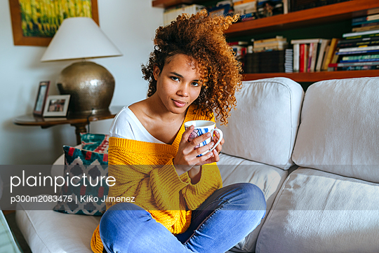 Portrait of attractive young woman with curly hair holding mug at home - p300m2083475 by Kiko Jimenez