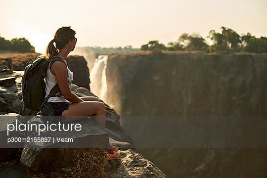 Woman sitting on the top of a rock enjoying the Victoria Falls at sunset, Zimbabwe - p300m2155897 by Veam