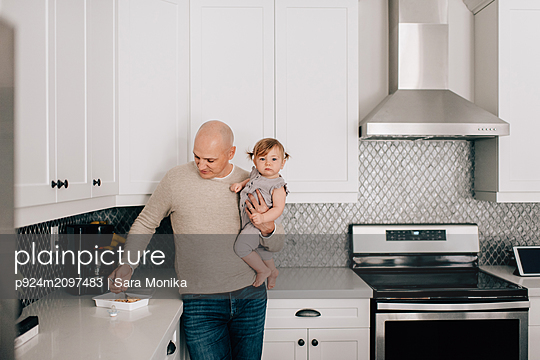 Father carrying baby daughter in kitchen, portrait - p924m2097483 by Sara Monika