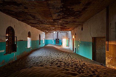 An abandoned building with boarded up windows, and shafts of sunlight lighting up the drifting sands and remnants of wall coloured green.  - p1100m1489983 by Mint Images