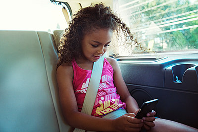 Girl using smart phone while traveling in car - p1166m1225971 by Cavan Images