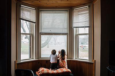 Rear view of siblings kneeling by window at home - p1166m1518911 by Cavan Images