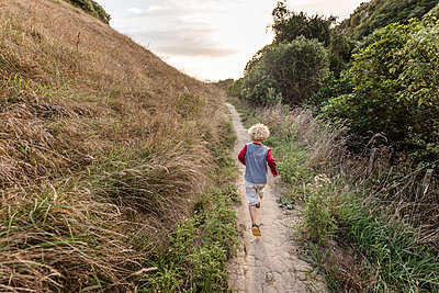 Toddler boy running on a hillside trail - p1166m2129487 by Cavan Images