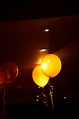 Balloons Resting Against Spotlight - p1248m2164304 by miguel sobreira
