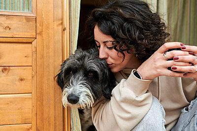 Mid adult woman kissing dog at doorway - p300m2282140 by Kiko Jimenez