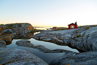 Wooden house on rocky coast - p312m1192835 by Peter Lyden