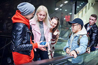 Young adult friends moving up underground station escalator  looking at smartphone - p429m1513803 by Gpointstudio