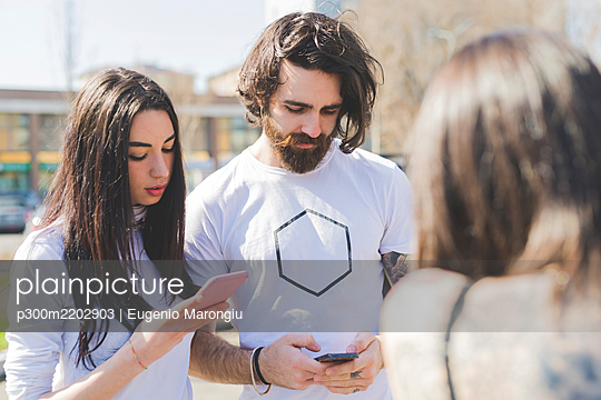 Young friends using smart phones while standing with woman in city - p300m2202903 by Eugenio Marongiu