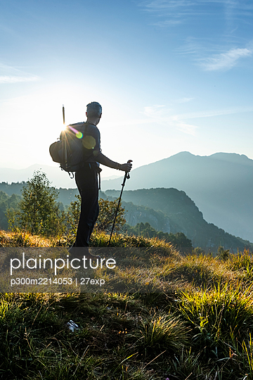 Silhouette male hiker looking at view while standing on mountain during sunrise, Orobie, Lecco, Italy - p300m2214053 by 27exp