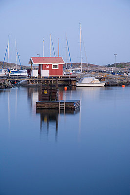 Calm and serene sea with a harbor in the background against clear sky - p1025m780039f by Björn Andrén
