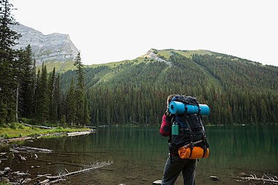 Man hiking with backpack along remote lake - p1192m1184076 by Hero Images