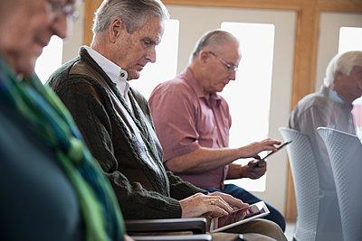 Focused senior man student using digital tablet in classroom - p1192m1212917 by Hero Images