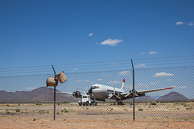 Douglas DC-4 Parked On Desert Like Ryan Airfield Behind Wire Fence With Buckets For Capturing Africanized Honey Bees  - p1291m1548107 by Marcus Bastel