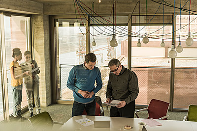 Business man showing document to colleague in office - p300m1356128 by Uwe Umstätter