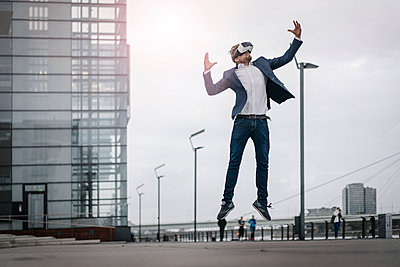 Businessman wearing VR glasses jumping in the city - p300m1536310 by Joseffson