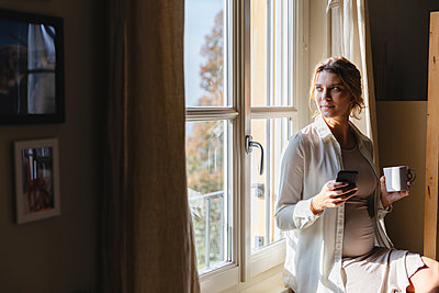 Young pregnant woman with coffee cup holding mobile phone while looking through window at home - p300m2243882 by Michela Ravasio