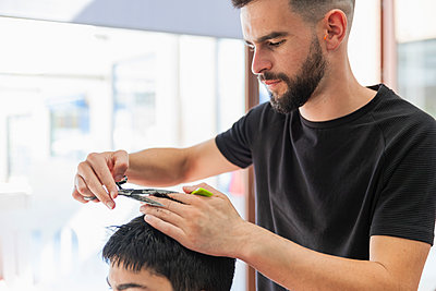 Male barber cutting hair of teenage boy at salon - p300m2275548 by Julio Rodriguez