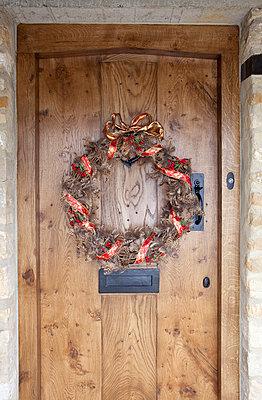 Christmas wreath on wooden doorway of Cotswolds home  UK - p3493478 by Robert Sanderson