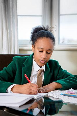 Black girl wearing school uniform doing homework - p555m1304049 by Alexander Robinson