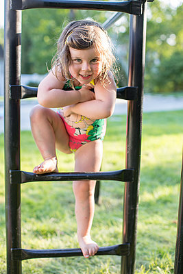 Portrait of girl in swimming costume standing on garden climbing frame - p924m1404252 by Sasha Gulish
