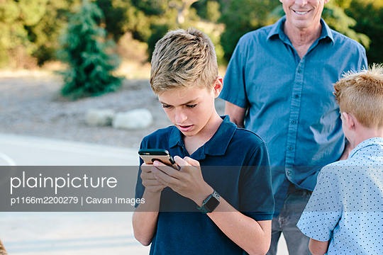Teen Boy Looks At His Smart phone While Outside With Family - p1166m2200279 by Cavan Images