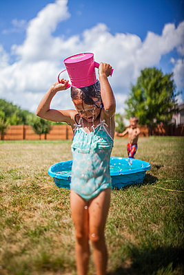 Girl pouring water on head while standing on grassy field at backyard - p1166m1474097 by Cavan Images