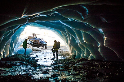 Couple exploring ice cave during helicopter tour. - p1166m2159594 by Cavan Images