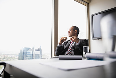 Pensive businessman looking out conference room window - p1192m1183751 by Hero Images
