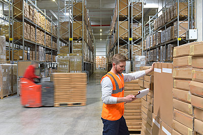 Man  with clipboard in factory hall and moving forklift - p300m1470034 by lyzs