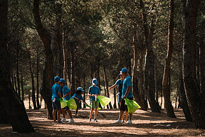 Group of volunteering children collecting garbage in a park - p300m2131965 von Jose Luis CARRASCOSA