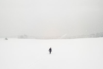 Woman walking alone in snow-covered landscape - p300m2180759 by Wilfried Feder