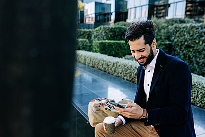 Smiling businessman using mobile phone while sitting on bench - p300m2256885 by Xavier Lorenzo