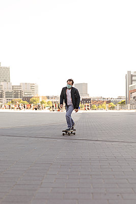 Man with community mask on skateboard, social distancing due to Covid-19 - p788m2184015 by Lisa Krechting