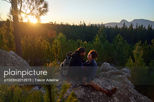 Happy affectionate young couple relaxing on rocks in woods at sunset - p1023m2212973 by Trevor Adeline