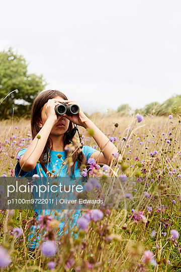 A girl holding binoculars, a young bird watcher standing in a meadow of tall grass and wild flowers. - p1100m972201f by Oliver Edwards