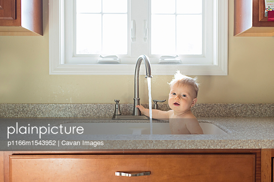 Portrait of shirtless baby boy playing with water while sitting in kitchen sink - p1166m1543952 by Cavan Images