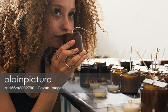 Female entrepreneur smelling craft candles in her workshop - p1166m2292790 by Cavan Images