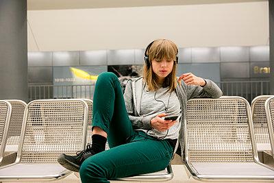Junge Frau mit Kopfhörer und Handy in der U-Bahnstation - p1212m1136997 von harry + lidy