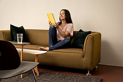 Woman sits on sofa reading book - p294m2132940 by Paolo