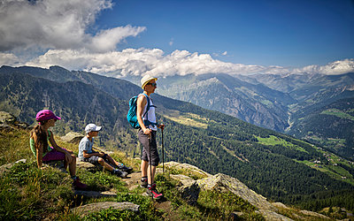 Mother with two children having a break from hiking in alpine scenery, Passeier Valley, South Tyrol, Italy - p300m2155559 by Dirk Kittelberger