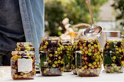 Man preparing olives in jars - p300m2242315 by VITTA GALLERY