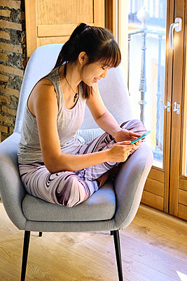 Woman using mobile phone while sitting on chair at home - p300m2264779 by Antonio Ovejero Diaz
