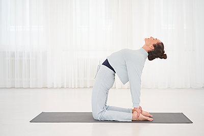 Woman practicing yoga in gym - p430m2244435 by R. Schönebaum