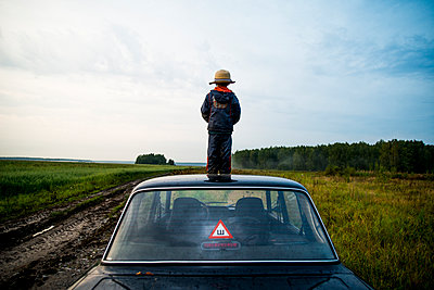 Caucasian boy standing on car roof in rural field - p555m1420567 by Aleksander Rubtsov